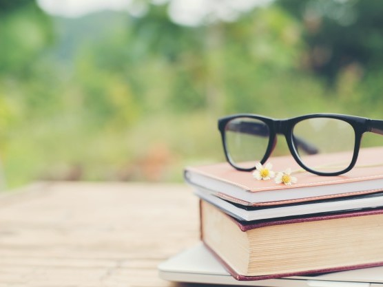 stack of books with pair of glasses on top